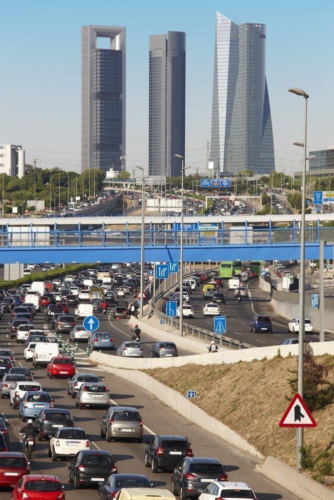 Mucho tráfico de coches a su paso por M-40. De fondo torres de Madrid