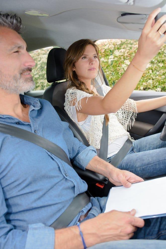 Mujer colocando retrovisor en examen practico de conducir
